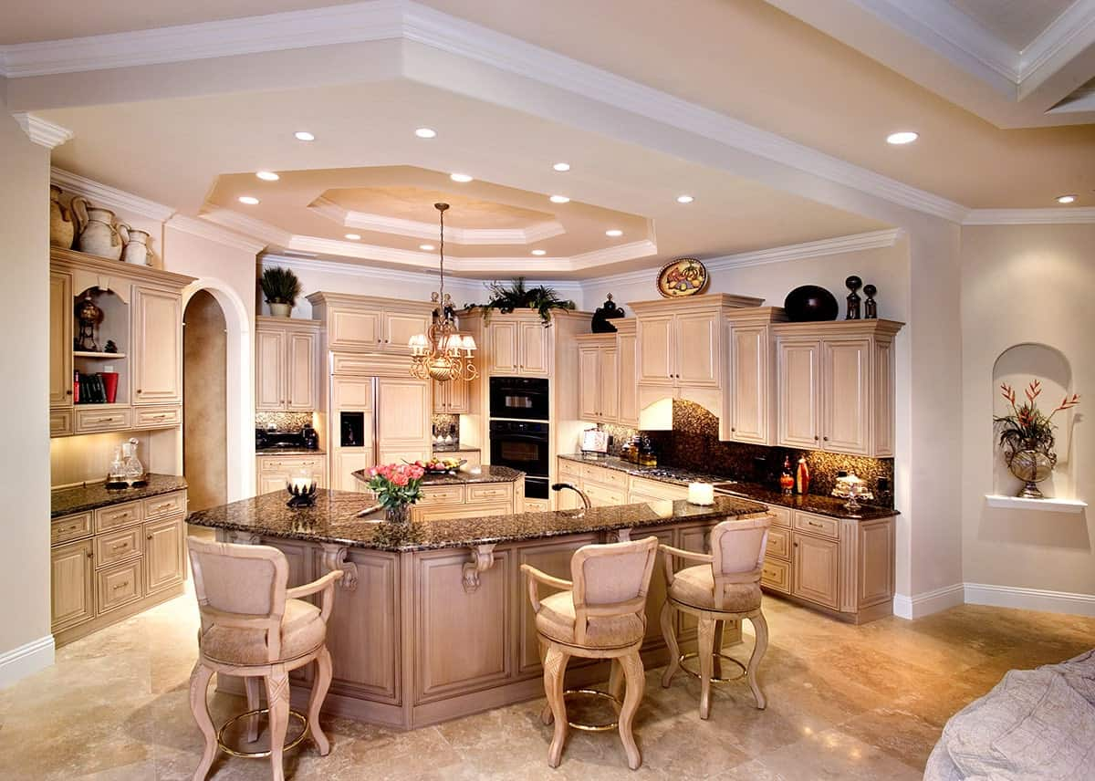 The elegant and homey Mediterranean-style kitchen has various decors and potted plants above the cabinets of the peninsula with a beige hue that matches the beige marble flooring as well as the beige wooden stools.