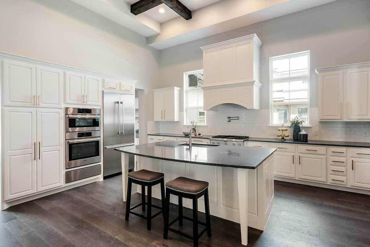 A Mediterranean-style kitchen with dark hardwood flooring that contrasts the island, peninsula and walls but matches with the exposed wooden beams of the white ceiling. These are augmented by the natural lights coming in from the windows flanking the vent hood.