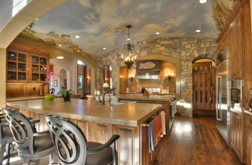 This is a charming and homey Mediterranean-style kitchen with a mural of the sky on the cove ceiling that complements the stone walls with arched entryways and an alcove for the cooking area. This matches perfectly with the wooden cabinetry and the hardwood flooring.