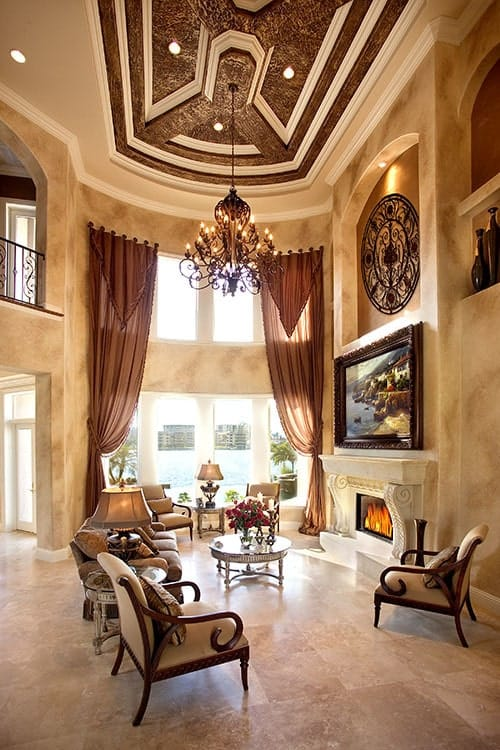 The elegant fireplace has a beige stone mantle with intricate designs that go well with the classic painting mounted above it. Across from this is a beige sofa paired with wooden armchairs that has the same beige hue as the tall wall that are augmented by the majestic chandelier as well as the tall windows.