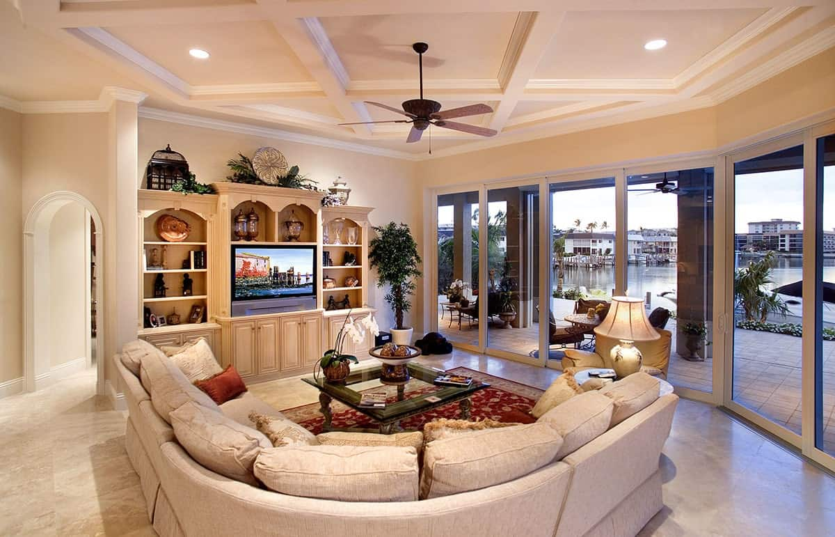 The beige L-shaped sectional sofa of this Mediterranean-style living room matches well with the beige wooden structure that houses the TV within its built-in shelves and cabinets. This is adorned with various decor and potted plants.