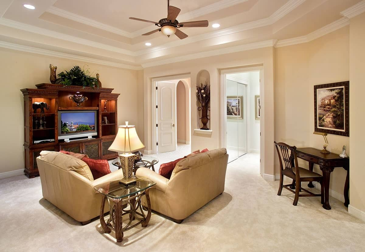 The beige carpeted flooring complements the light brown leather armchairs flanking the glass-top end table bearing a table lamp. The beige walls of this living room are adorned with an arched alcove with a flower vase that is flanked by two doorways.