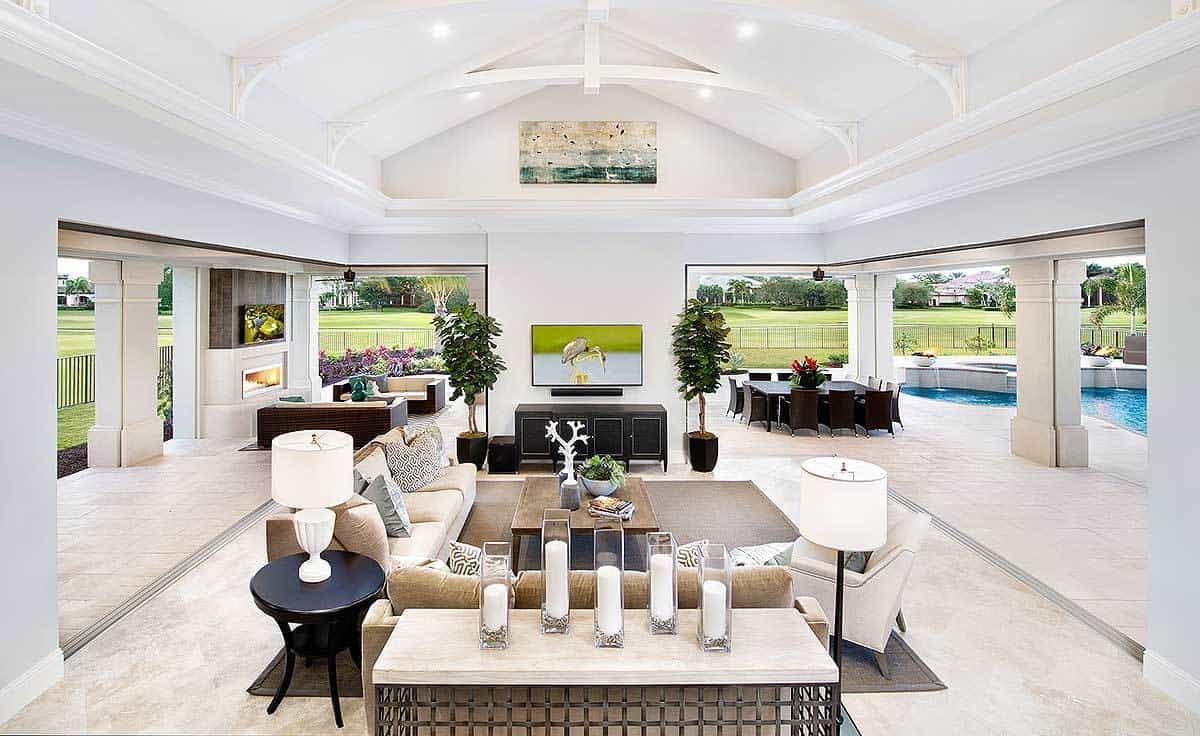 The white cathedral ceiling of this Mediterranean-style living room shines with the recessed lights as well as the natural lights coming in from the open walls adorned with thick white pillars. The brightness is contrasted by the brown area rug and the beige sofas.