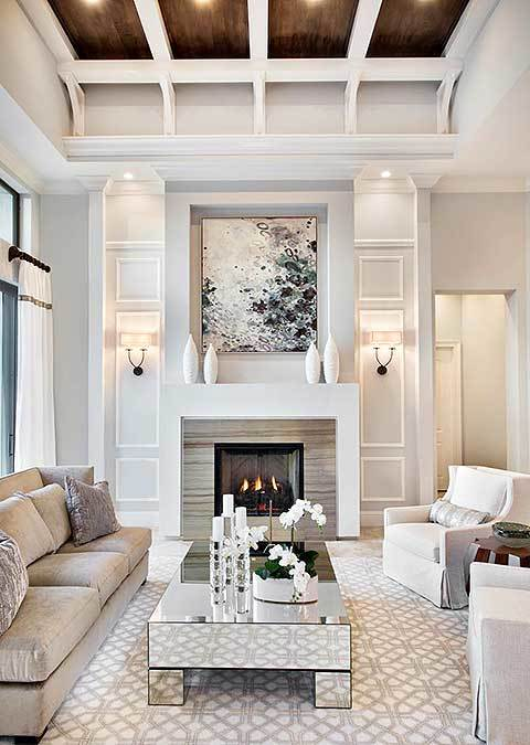 This Mediterranean-style living room has a mirrored coffee table that gives accent to the patterned light gray area rug that is complemented by the gray cushioned sofas. This setup has a nice background of a fireplace housed in a white wall augmented by a colorful painting.
