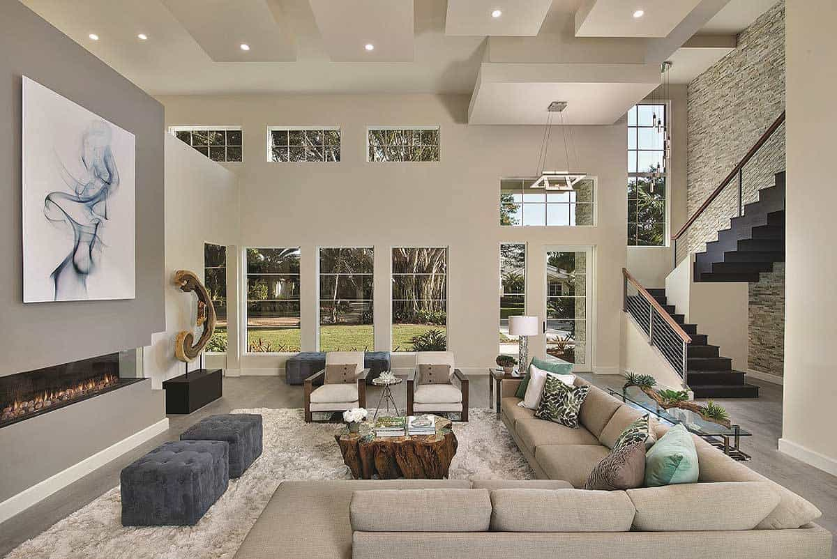 The high ceiling of this Mediterranean-style living room is augmented by a row of wide transom windows that matches well with the tall windows that showcase a lovely scene outside that give color to the simple gray L-shaped sectional sofa and gray modern fireplace.