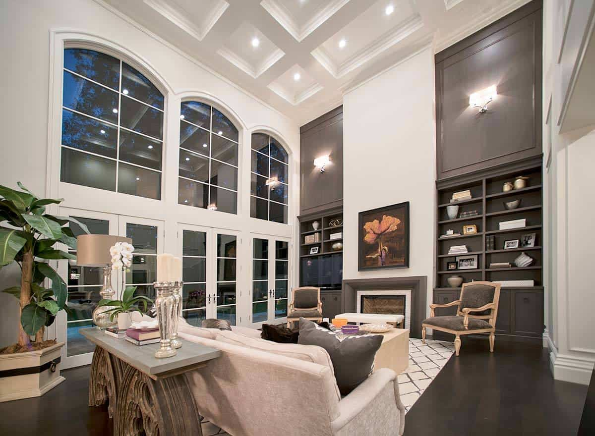 The high white coffered ceiling of this living room is paired with a row of tall arched windows that dominate this grand room. This is gives those sitting on the beige sofa a sense of being in a wide spacious place warmed by a fireplace with a brown mantle.