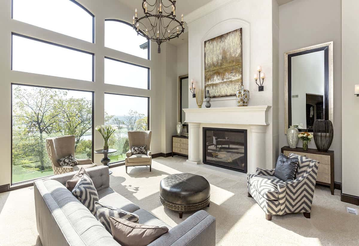 The lovely fireplace that has a glass enclosure is adorned with a white mantle that has a pair of pillars in its design. This is topped with a colorful painting that is brightened by the two large arched windows that bring in sunlight to the beige carpeted flooring and gray sofa.