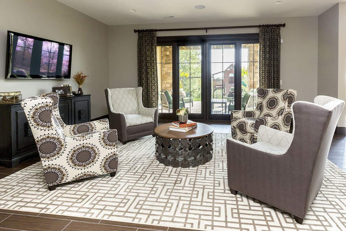 This charming and cozy living room is dominated by the different patterns of the white area rug that contrasts the dark flooring tiles as well as the cushions of the armchairs surrounding the brown circular coffee table that matches with the dark wooden entertainment cabinet.