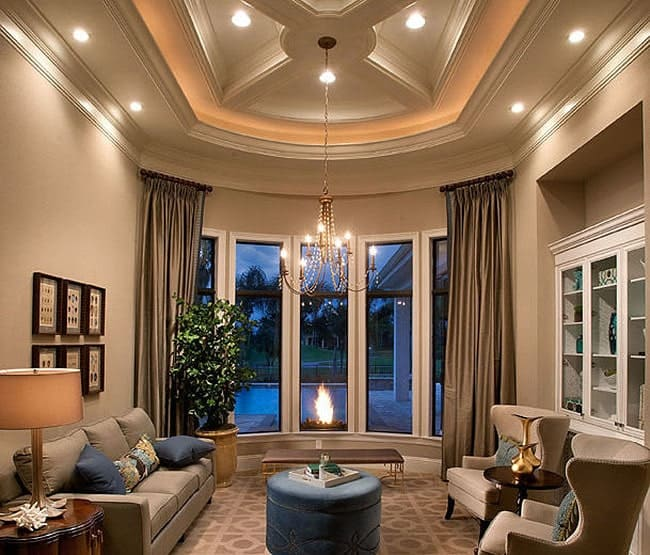 This Mediterranean-style living room has a beautiful coffered ceiling that has recessed lights as well as a thin chandelier hanging over the blue cushioned ottoman in the middle of the patterned light gray carpet that pairs well with the gray sofa and the two wing back armchairs.