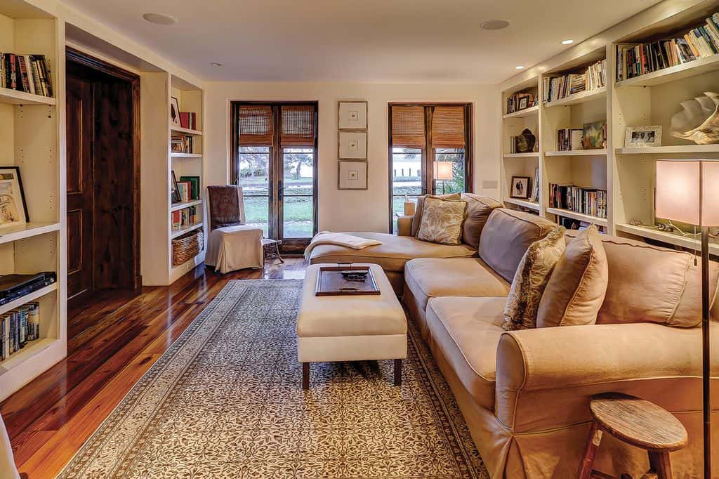 This homey and comfortable Mediterranean-style living room is surrounded by bookshelves that are built into the white walls. This is contrasted by the hardwood flooring that is topped with a complex patterned area rug that goes well with the brown L-shaped sectional sofa.