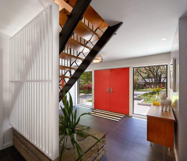 This is a Mid-Century Modern foyer with a bright red-orange double doors to serve as the main entry. This is flanked by two brilliant floor-to-ceiling glass windows that brings an abundance of natural lights onto the dark flooring tiles adorned with a planter under the stairs.