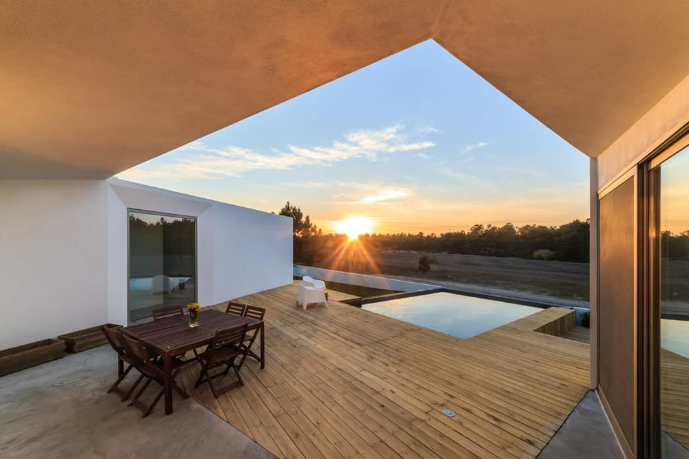 Modern house featuring a deck near the swimming pool area. It also features a square dining table set for six.
