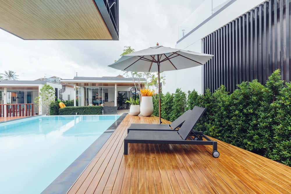 Stylish bungalow-style house featuring a side-pool deck with modish lounger seats.