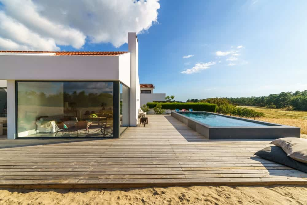 This modern house features a large deck surrounding the stylish rectangular pool.