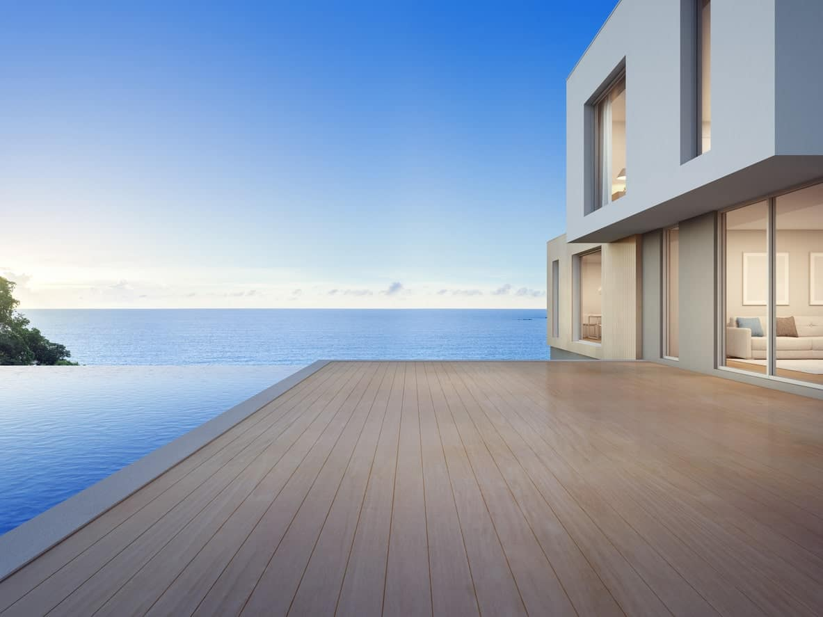 Large modern home featuring an infinity pool and a large deck overlooking the stunning ocean.