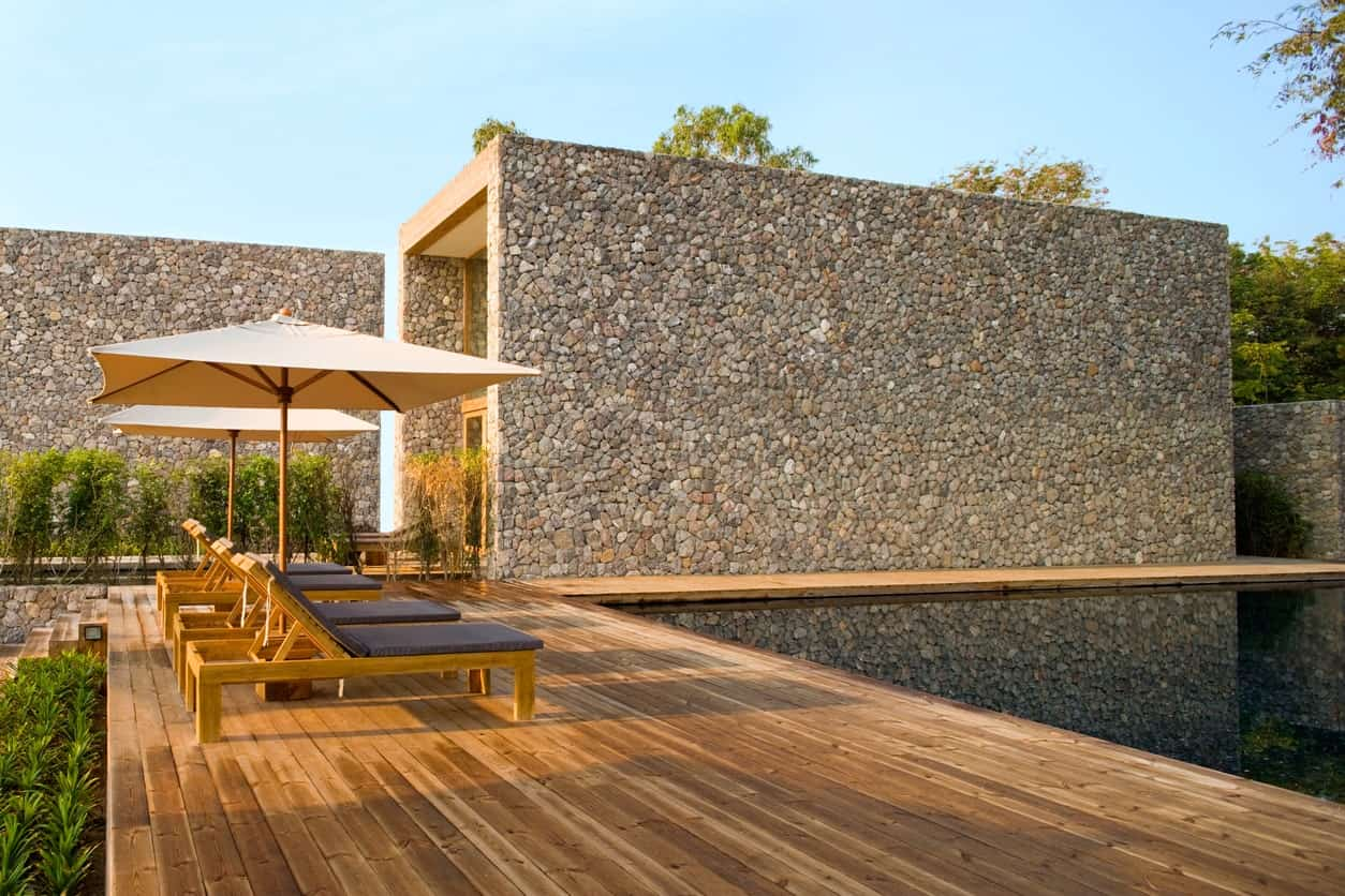Stunning modern home with a large deck featuring a set of lounger seats with umbrellas.