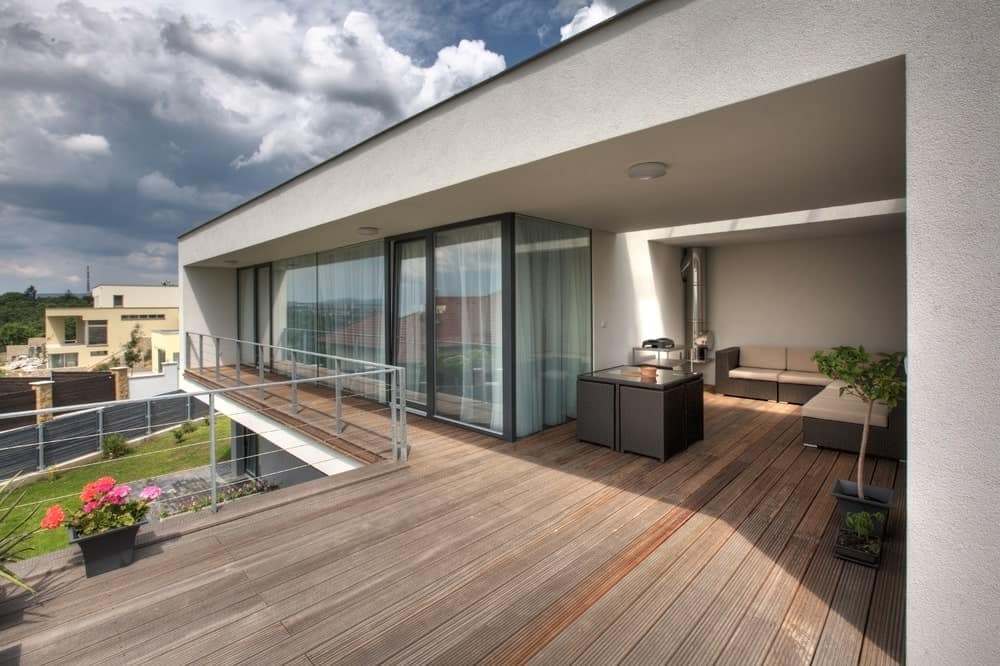 This modern house offers a deck set on the second floor. The deck also features a patio area.