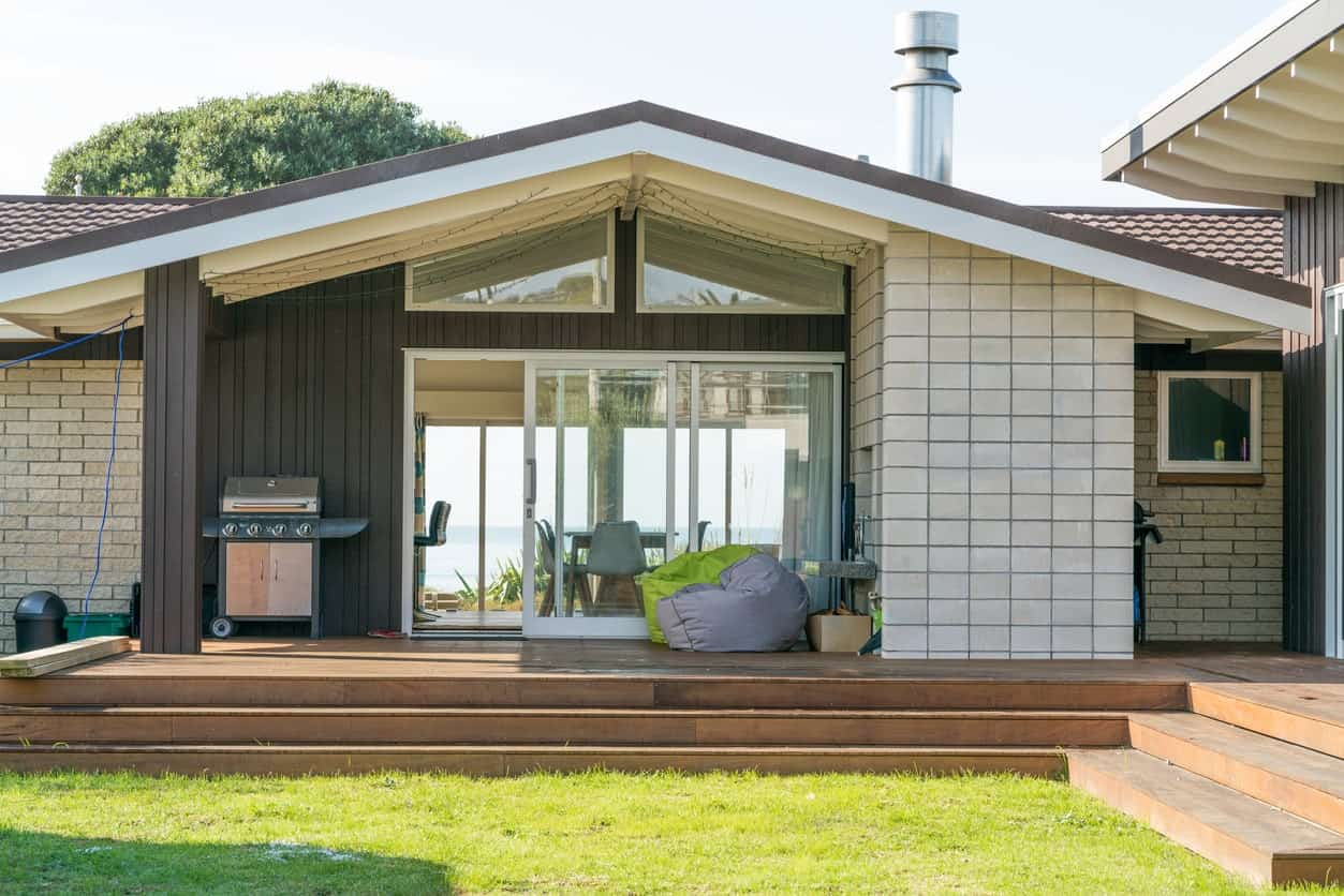 Modern house featuring a deck surrounded by the lawn and garden area.