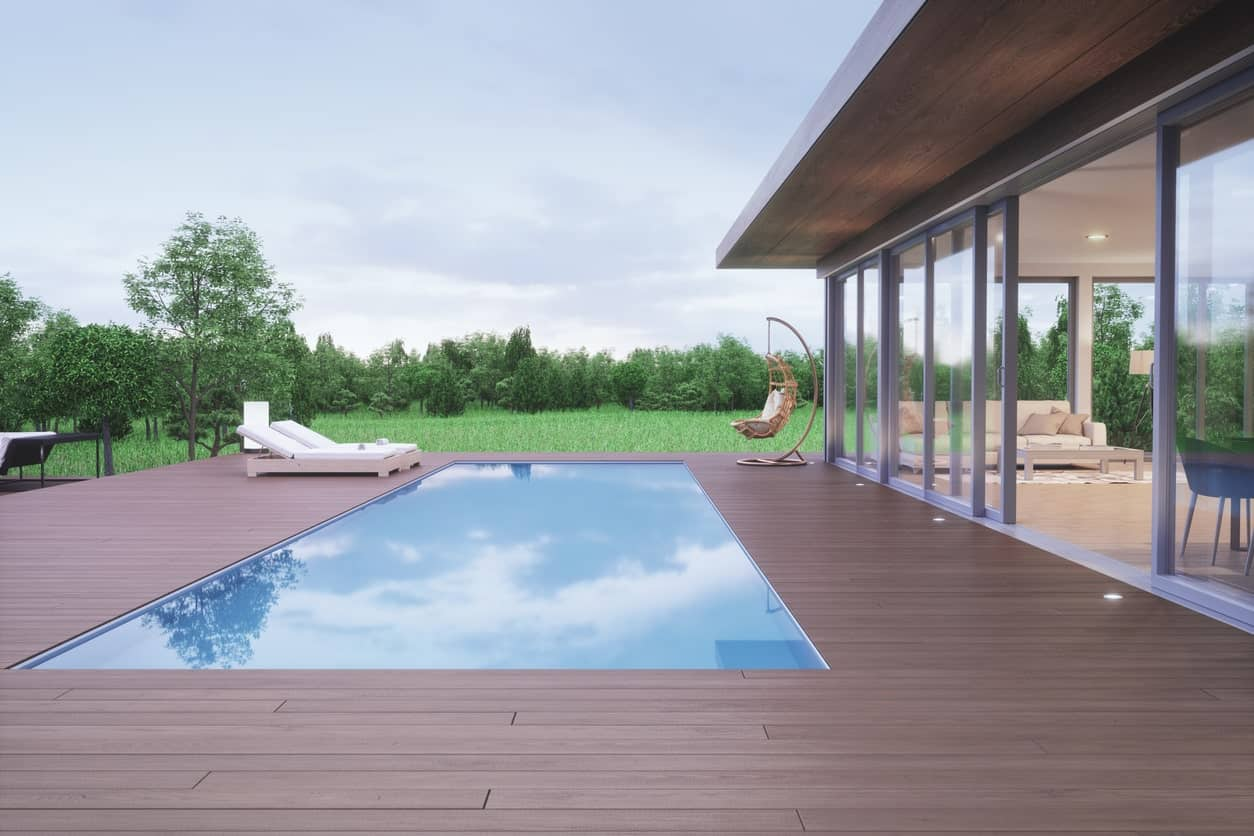 This modern bungalow-style home features a deck surrounding the stylish pool.