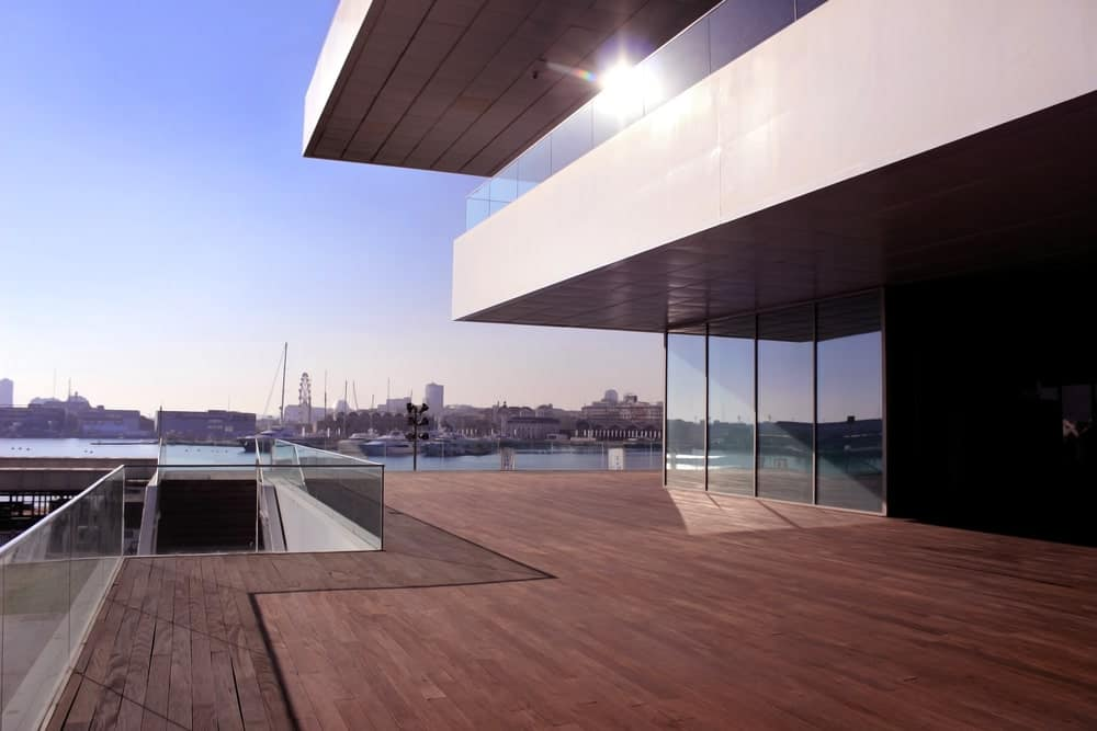 Large modern house featuring a massive deck area with glass railings.