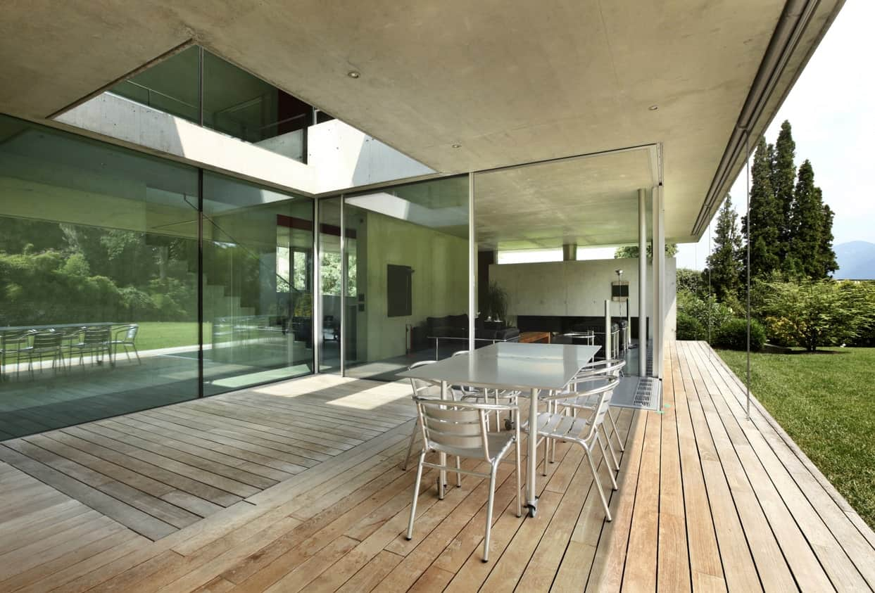 Modern house with a large deck featuring a dining table set overlooking the beautiful garden area.
