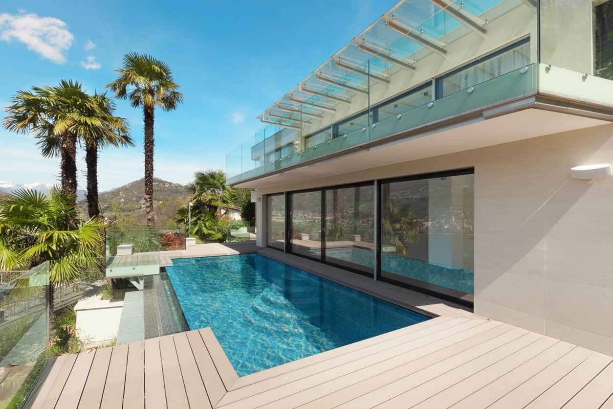 A modern house featuring a deck surrounding the stunning pool. The deck also features glass railings.