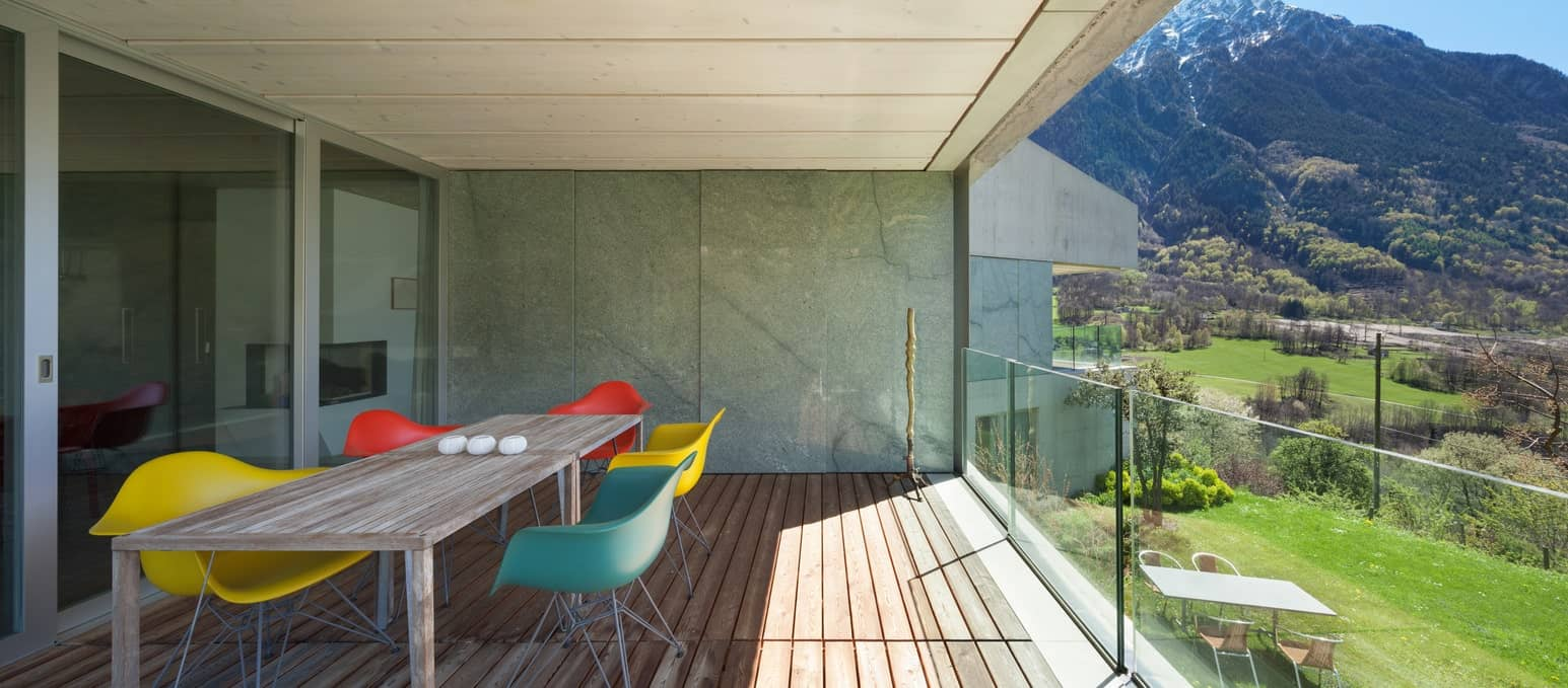 A modern deck featuring glass railings and a dining table set. The beautiful surrounding can be overlooked in this area.