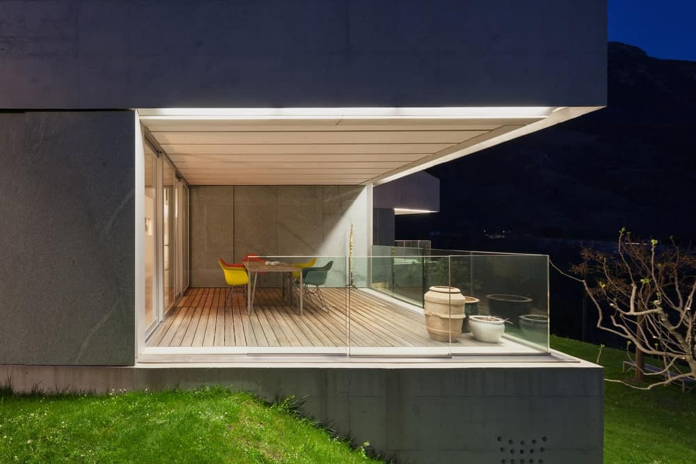 This modern deck balcony boasts glass railings along with a rectangle dining table set.