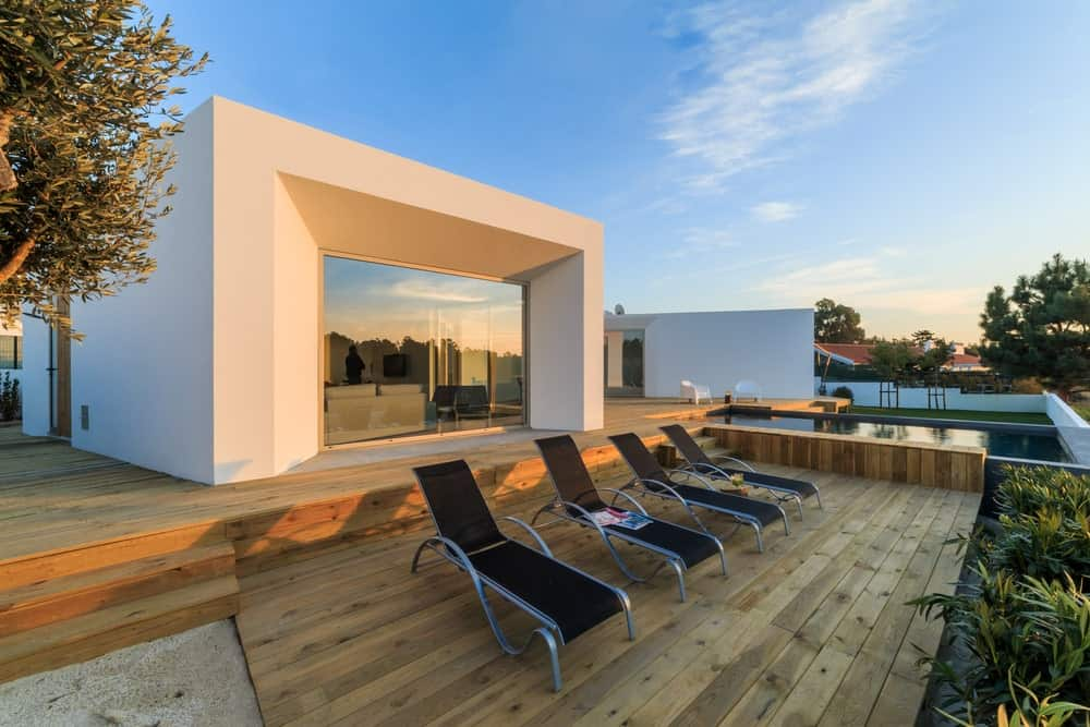This home offers a deck and swimming pool with a coffee table set and lounger seats.