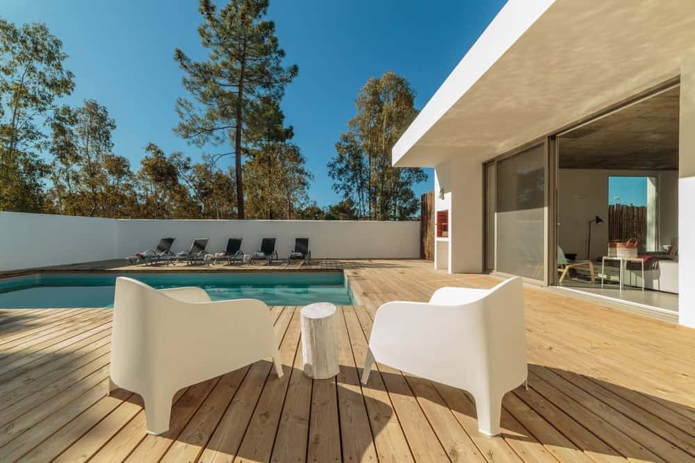 Large deck area featuring a coffee table set for two and five lounger seats surrounding the swimming pool.