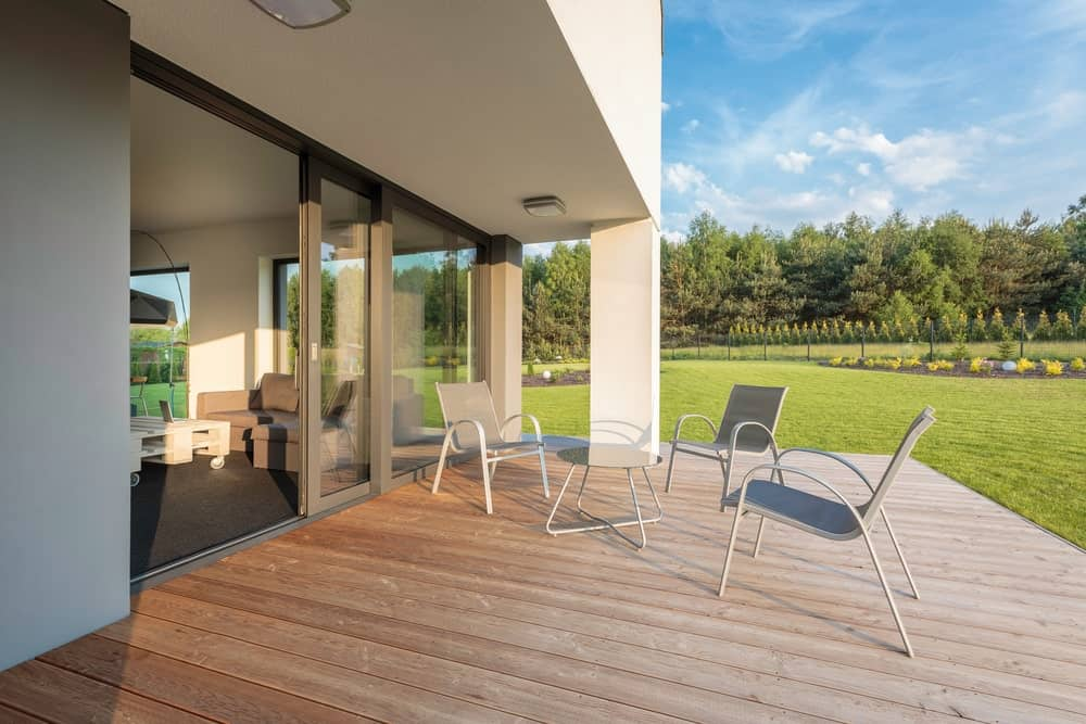 This deck offers a coffee table set with three seats overlooking the beautiful garden area of the property.
