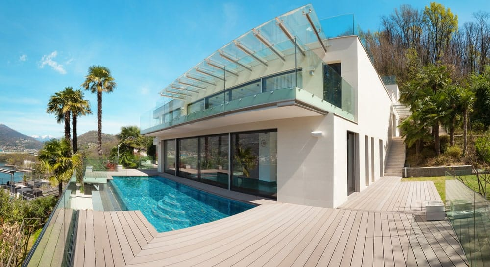 Modern mansion featuring a large deck area with a small swimming pool set on the center.