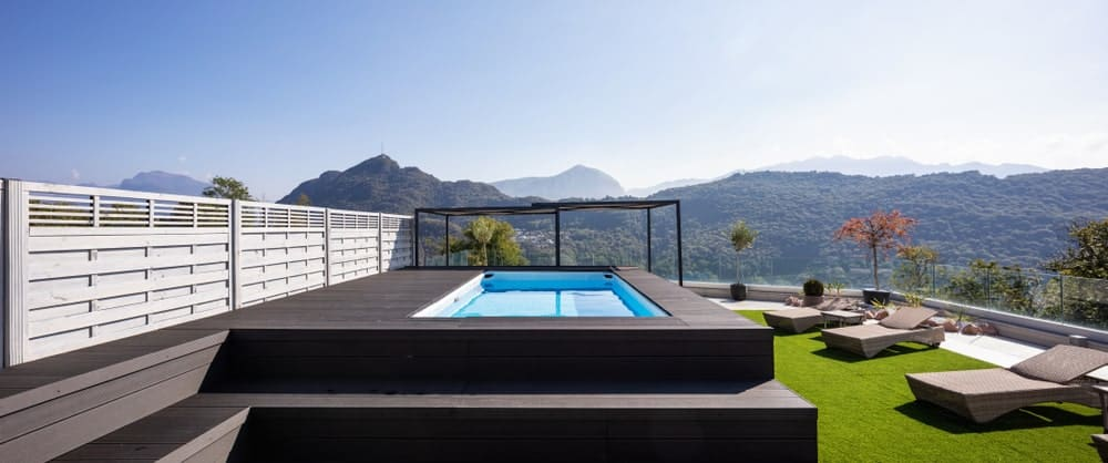 This modish deck set on the property's garden and lawn area leads to the rectangular swimming pool.
