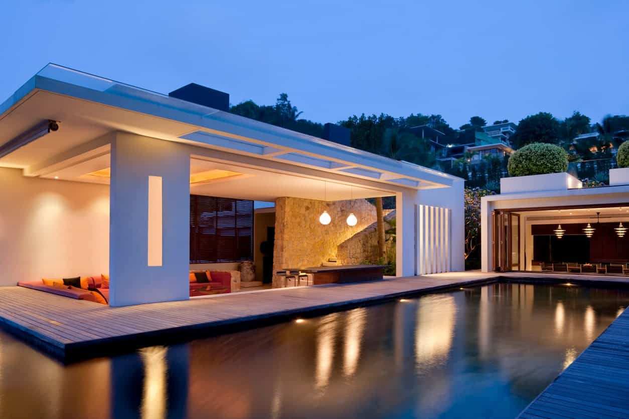 Classy modern house with a large deck surrounding the pool. The deck also leads to the home's lounging space.