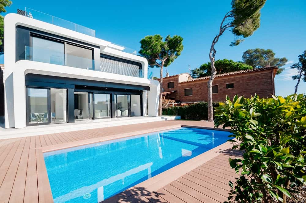 This white modern home has a stunning yard featuring a deck and a swimming pool.