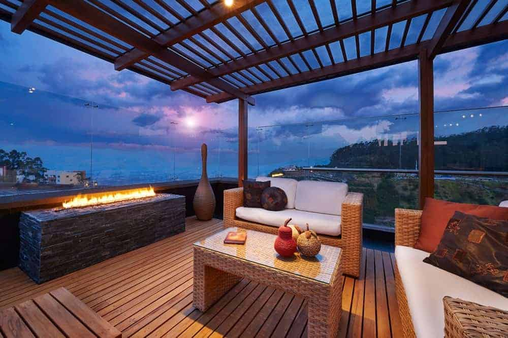 Elegant deck featuring rattan seats with foam seats and backrests along with a stylish fire pit.