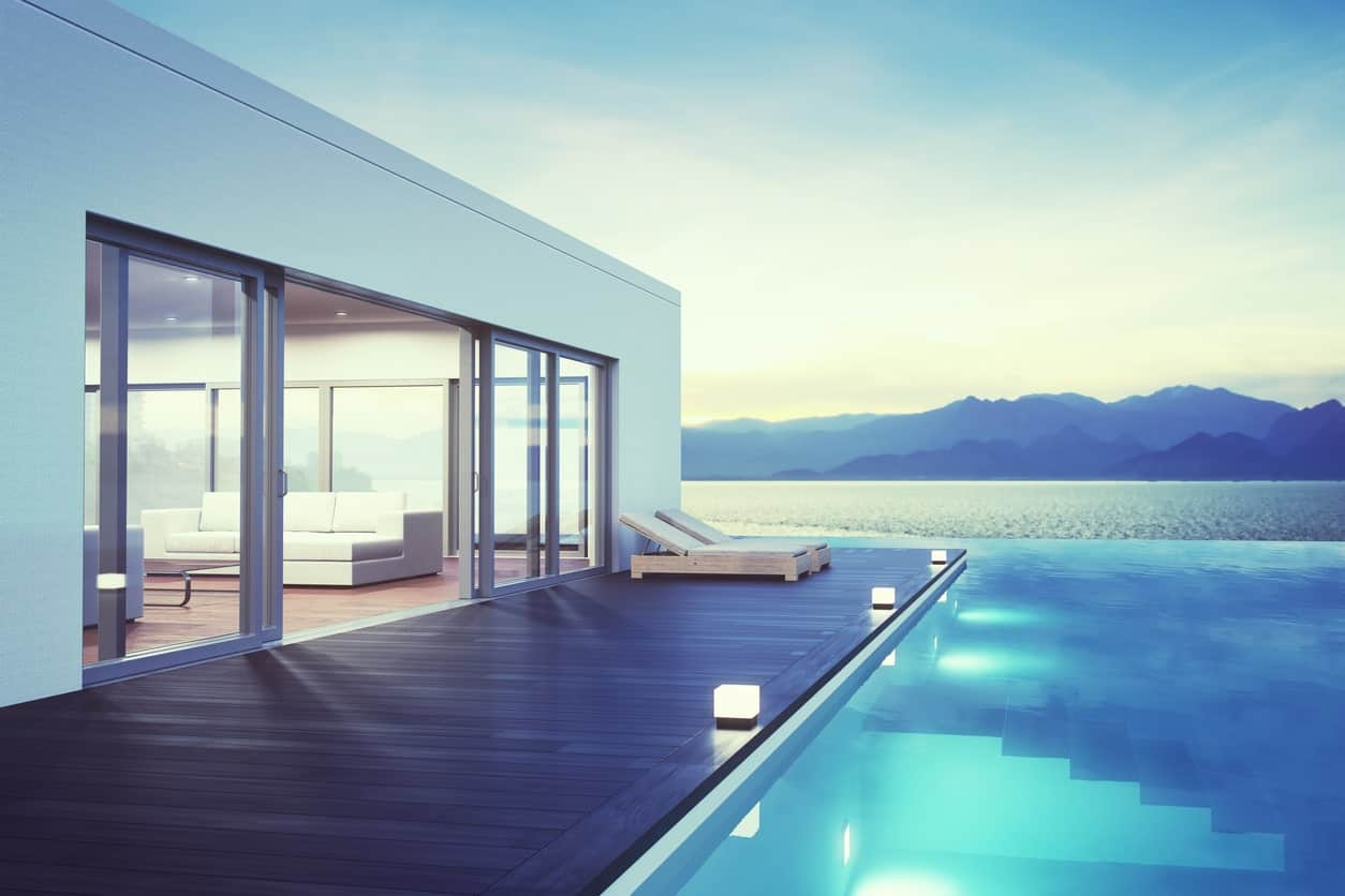 Modern pool-side deck with a couple of lounger seats overlooking the beautiful surrounding.