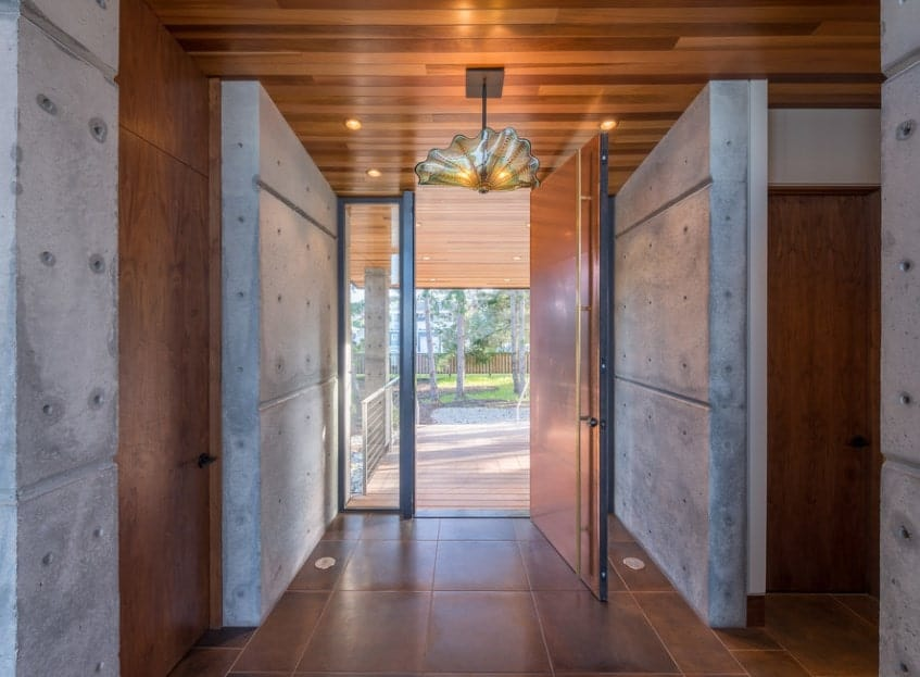 This Modern-style foyer has earthy brown floor tiles that matches with the dark brown main door, wall panel and the wooden ceiling. These are complemented by the gray concrete walls that are brightened by the natural lights coming in from the open door and its glass side lights.