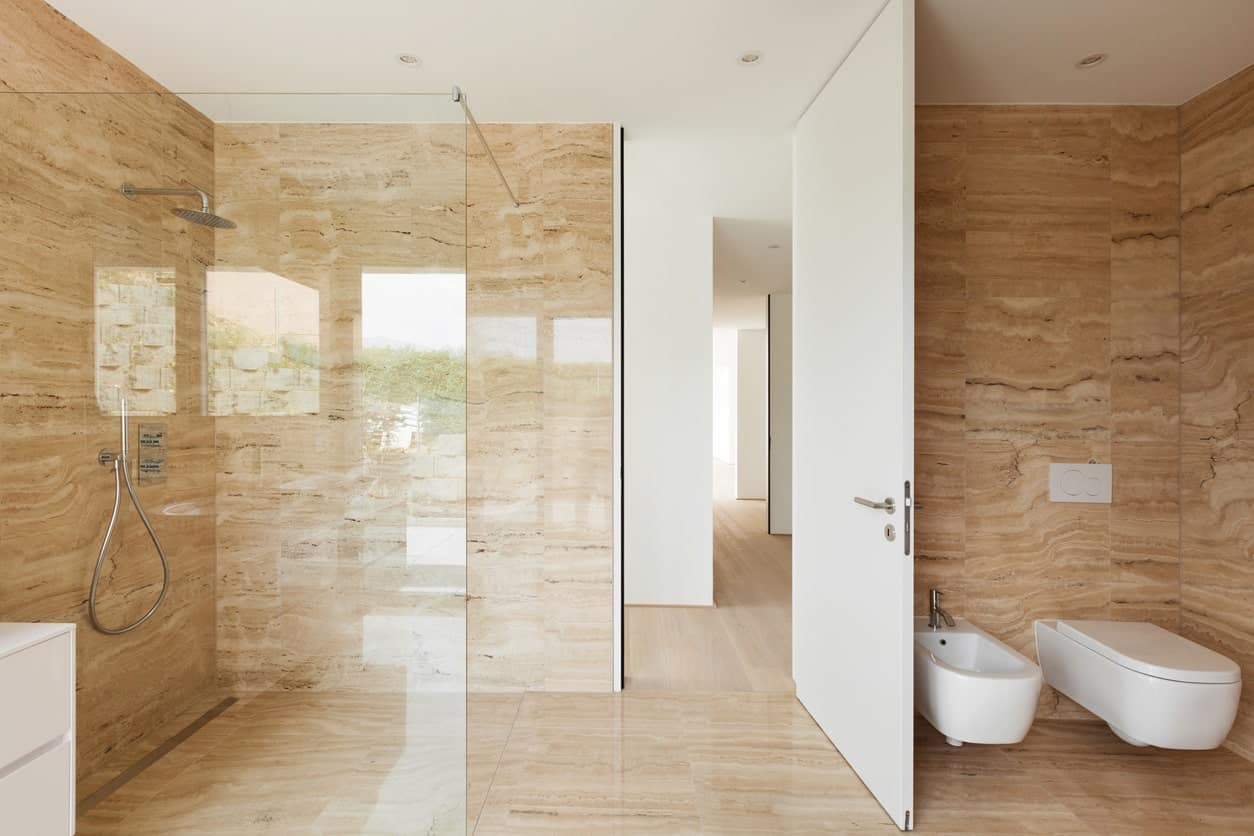 This large bathroom features matching tiles walls and floors. There's a corner open shower too.