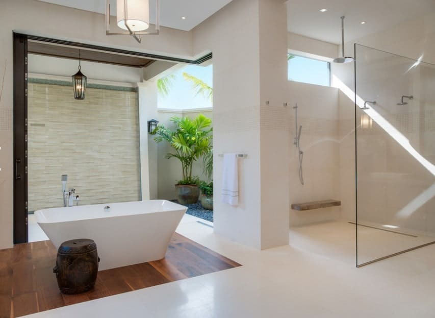 This primary bathroom offers a freestanding tub and an open shower in the corner, surrounded by white walls and floors.