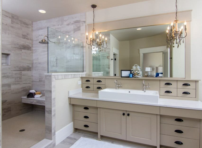 This bathroom boasts a large vessel sink lighted by glamorous chandeliers. The open shower room features stylish walls.
