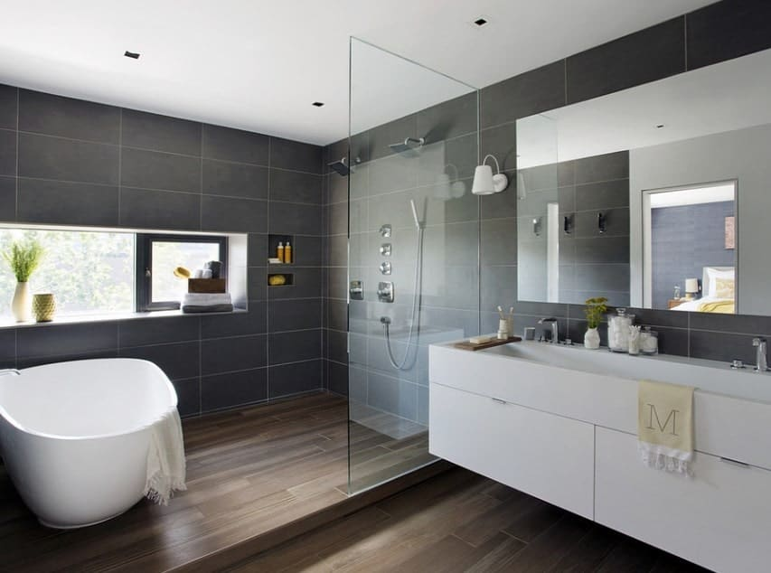 This primary bathroom boasts black tiles walls and hardwood flooring, along with a soaking tub and floating vanity sink counter.