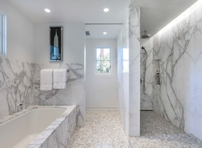 This primary bathroom boasts luxurious walls made of stylish marble. There's a large bathtub and an open shower room.