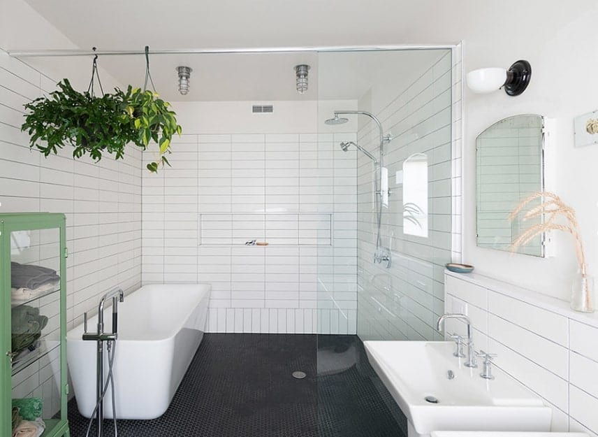This primary bathroom boasts white tiles walls, white freestanding tub and a white pedestal sink. There's an open shower space as well.