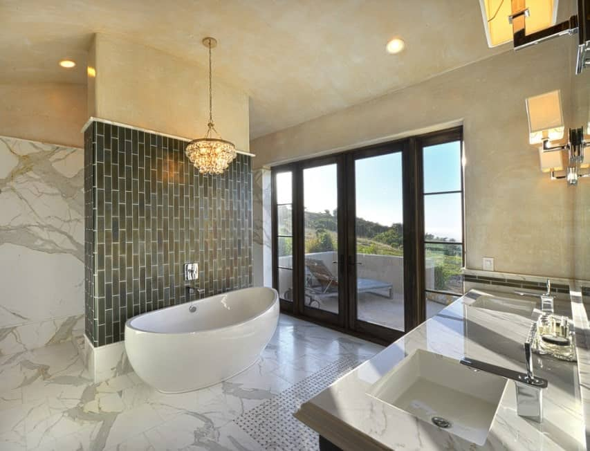 This primary bathroom boasts marble tiles floors and walls, matching the marble sink countertop. The freestanding tub is lighted by a glamorous chandelier.