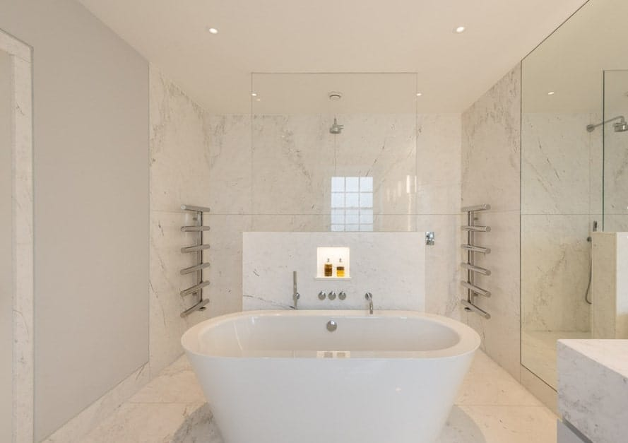 The large freestanding tub and an open shower space are surrounded by white marble tiles floors and walls.