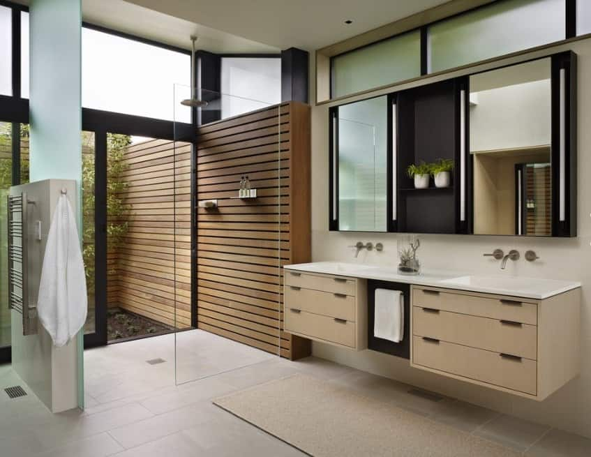 Large and modish primary bathroom with floating vanity sink counter and an open shower area.