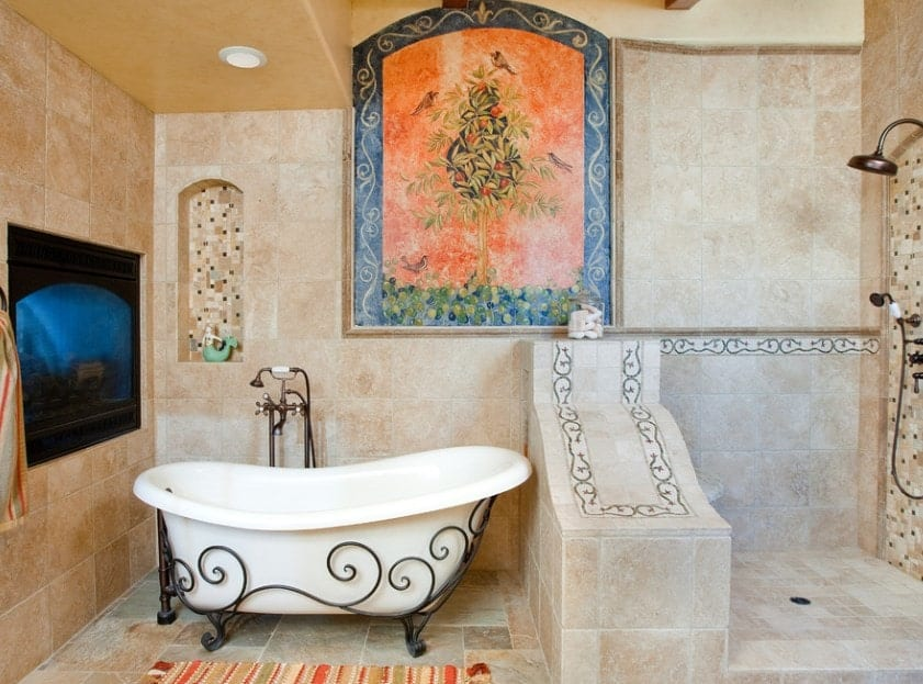 This luxurious primary bathroom boasts tiles floors matching the tiles walls with lovely decor. The freestanding tub looks classy together with the open shower room.