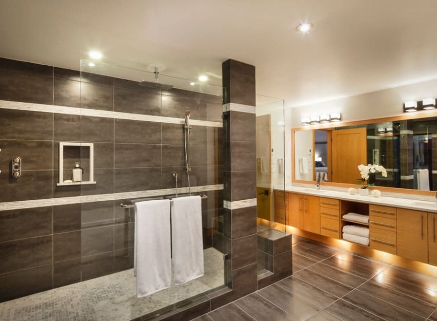 An elegant primary bathroom with brown tiles walls matching the brown tiles floors lighted by wall and ceiling lights. There's an open shower room set on the side.