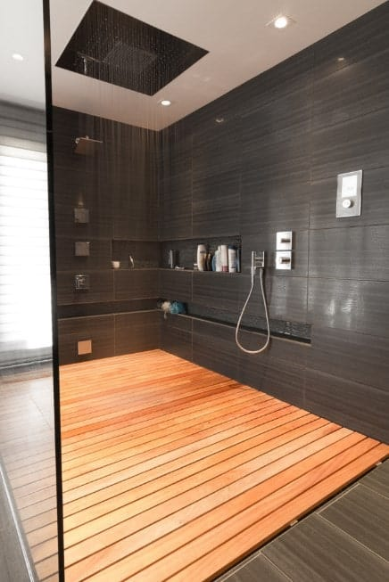 This luxurious primary bathroom offers a stunning shower room surrounded by black tiles walls and hardwood floors.